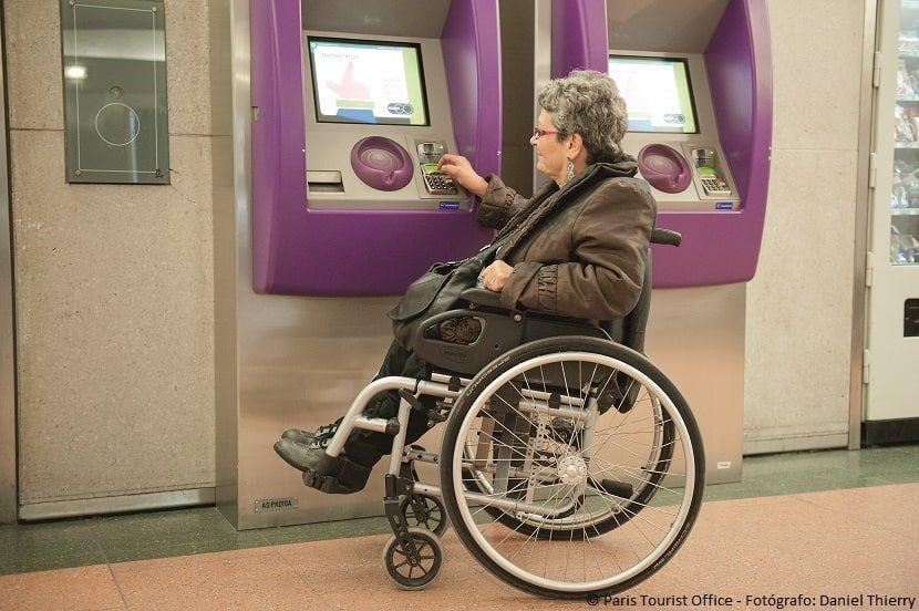 Mujer en silla de ruedas sacando un billete de metro en París